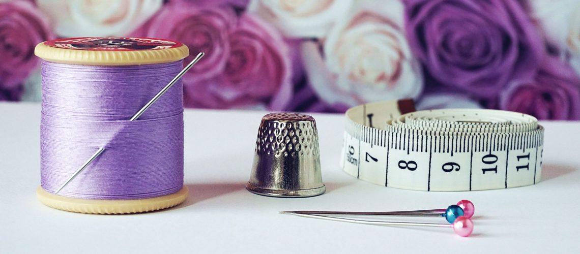 spool-of-purple-thread-near-needle-thimble-and-measuring-1266139